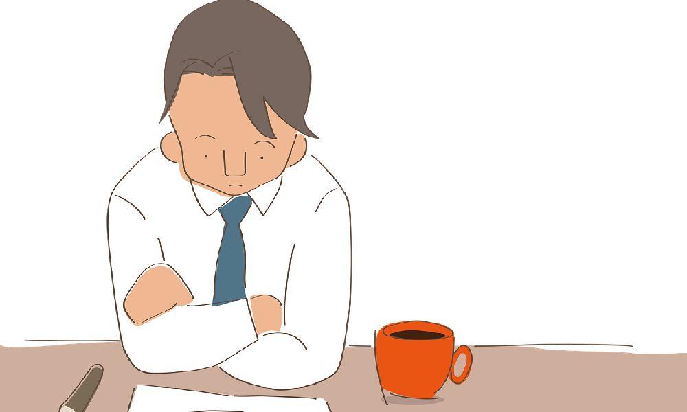 料金が妥当かどうかを机に向かって座り、腕を組んで考えるスーツの男性