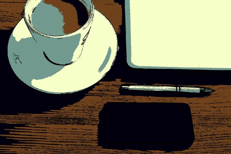 彼女の机の上に置かれた黒いiphoneとコーヒーカップとノートPC
