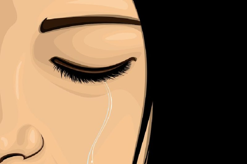 我慢し過ぎて涙が止まらない目を閉じて泣く女性