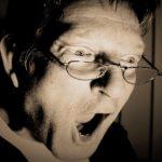 妻のスマートフォンを見て驚き、衝撃を受けるメガネを掛けた夫